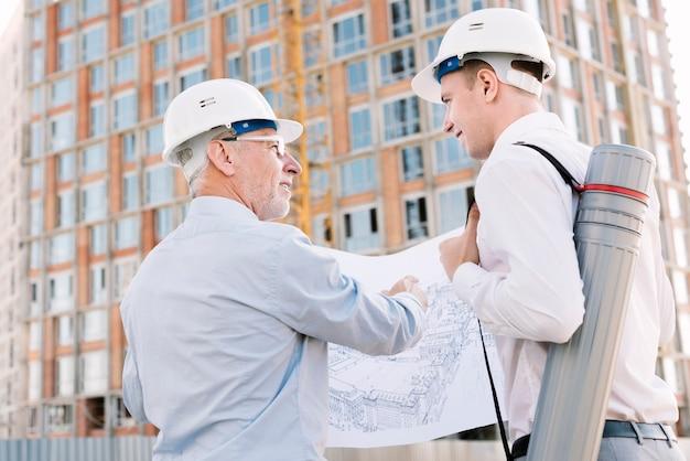 Vista lateral de personas con dibujo de construcción