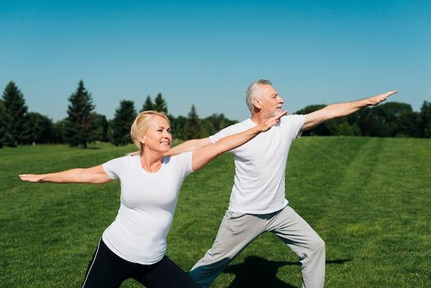 Vista lateral de personas mayores haciendo ejercicio al aire libre