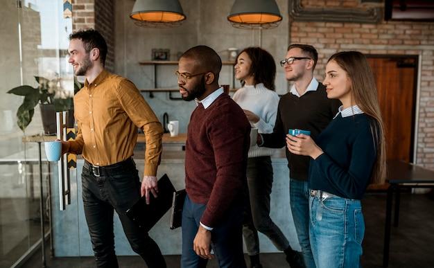 Vista lateral de personas reunidas tomando café