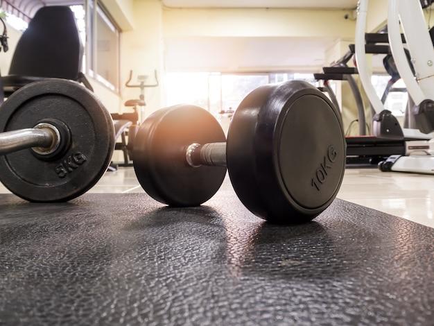 Vista lateral de la pesa en el piso en el gimnasio de fitness