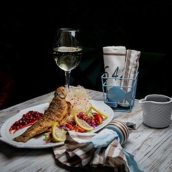 Vista lateral pescado frito con copa de vino y limón y servilletas en plato blanco