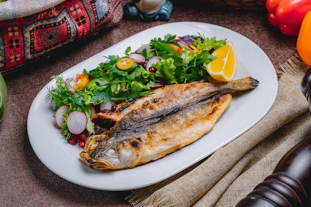Vista lateral de pescado a la parrilla con una ensalada de verduras y hierbas con una rodaja de limón