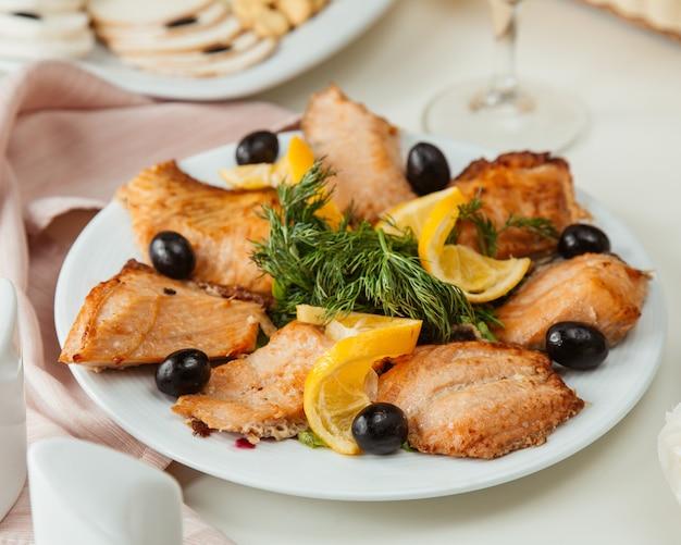 Vista lateral de pescado a la plancha con limón y verduras