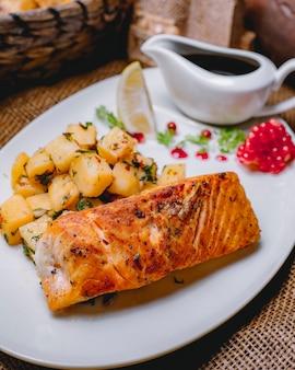 Vista lateral pescado rojo frito con papas y una rodaja de limón con salsa de granada
