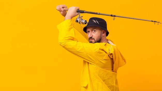 Vista lateral del pescador sosteniendo la caña de pescar con espacio de copia