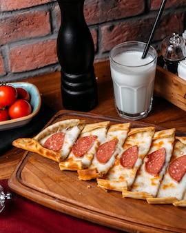 Vista lateral de pide turco con salchichas de salami dispuestas sobre una tabla para cortar madera