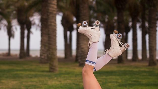 Vista lateral de la pierna de una mujer con patín blanco contra el árbol