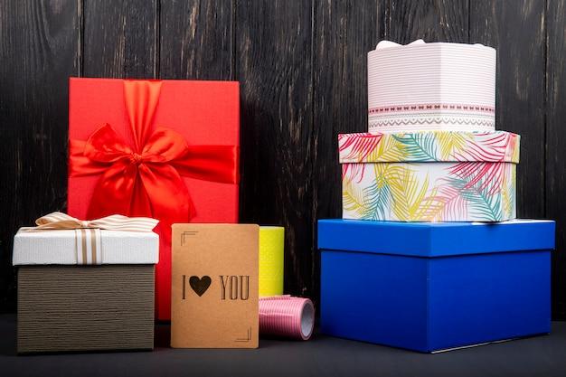 Vista lateral de una pila de cajas de regalo coloridas y una pequeña tarjeta de te amo en la mesa de madera oscura
