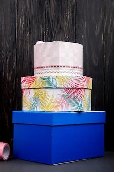 Vista lateral de una pila de coloridas cajas presentes en la mesa de madera oscura