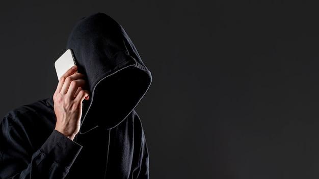 Vista lateral del pirata informático masculino hablando por teléfono inteligente con espacio de copia