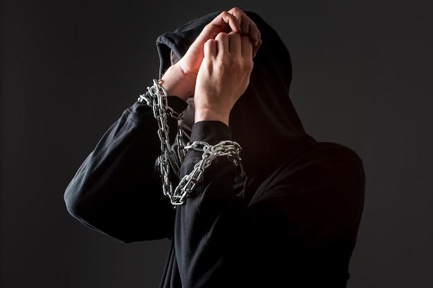 Vista lateral del pirata informático masculino con las manos atadas por la cadena
