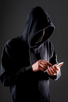 Vista lateral del pirata informático masculino con teléfono inteligente