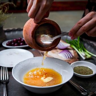 Vista lateral piti en olla de barro con plato hondo y cebollas verdes y mano humana y cuchara en bandeja de cobre en el restaurante