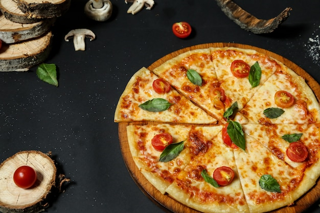 Vista lateral de pizza en una bandeja con tomates y champiñones sobre una mesa negra