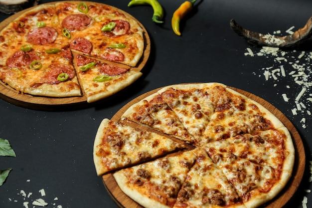 Vista lateral pizza de carne en una bandeja con pizza de salami y pimientos picantes en mesa negra