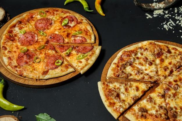 Vista lateral pizza de carne con pizza de salami en puestos con pimiento picante