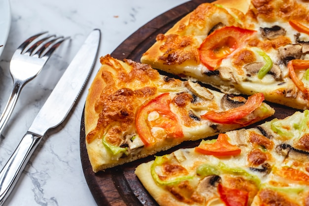 Vista lateral pizza de champiñones con tomate pimiento queso y champiñones