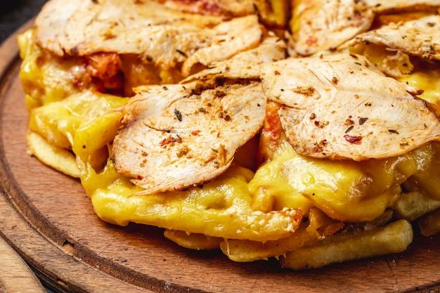 Vista lateral pizza de papas fritas con pollo asado, queso derretido y seaspning en un tablero
