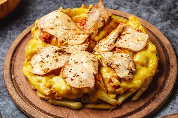 Vista lateral pizza de papas fritas con queso derretido pollo asado y condimentos en un tablero