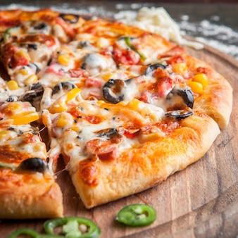 Vista lateral de pizza con pimiento picado en utensilios de cocina