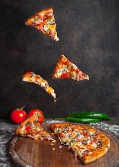 Vista lateral de pizza con pimiento y tomate y rebanadas de pizza en utensilios de cocina