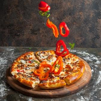 Vista lateral de pizza con rodajas de pimiento y rebanadas de pizza y harina en utensilios de cocina