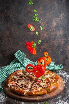 Vista lateral de pizza con rodajas de pimiento y rodajas de pizza en utensilios de cocina