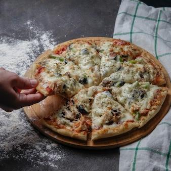 Vista lateral de pizza en un soporte de madera con un mantel, mano tomar una rebanada de pizza