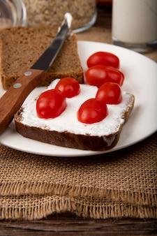 Vista lateral de la placa con rebanada de pan de centeno requesón y tomates con cuchillo en la superficie de tela de saco