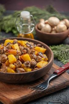 Vista lateral del plato de aceite y ramas cuenco marrón de papas con champiñones en la tabla de cortar junto al tenedor debajo del cuenco de aceite de champiñones blancos y ramas de abeto