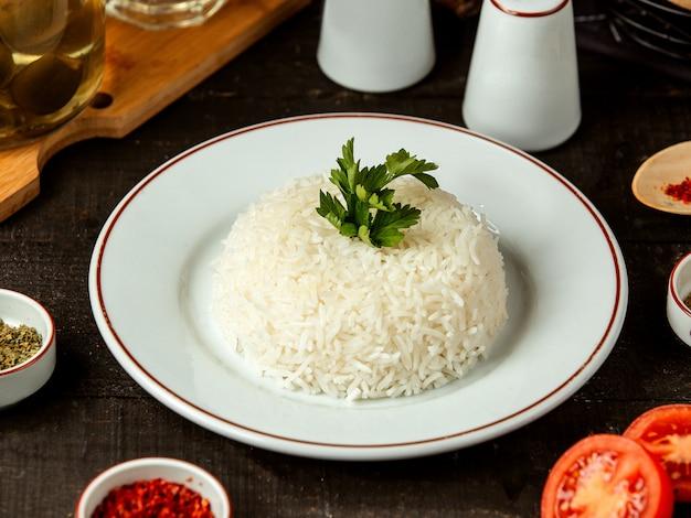 Vista lateral de un plato con arroz cocido con perejil sobre la mesa