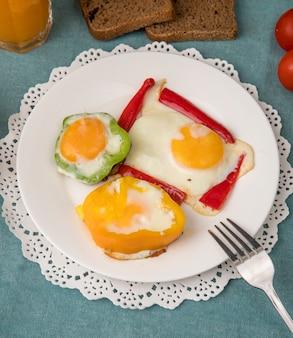 Vista lateral del plato de desayuno con huevos y pimientos en tapete de papel con un tenedor sobre fondo azul.