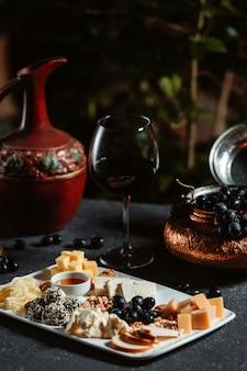 Vista lateral del plato de queso servido con uva y miel en mesa negra