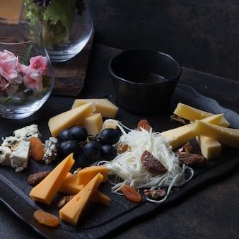 Vista lateral plato de queso con uvas y nueces y miel en bandeja