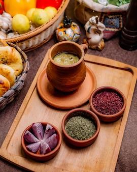Vista lateral de un plato tradicional azerbaiyano piti en una olla con hierbas secas de zumaque y cebolla en una bandeja