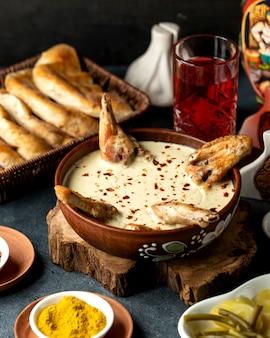 Vista lateral de pollo al horno con queso en un recipiente de arcilla