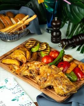 Vista lateral pollo al tabaco frito con papas y verduras a la parrilla sobre una tabla de madera