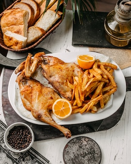 Vista lateral de pollo asado con papas fritas en un plato blanco sobre una tabla para cortar madera