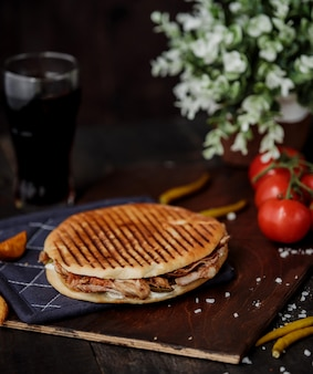 Vista lateral del pollo doner kebab en pan de pita y sobre una tabla de madera y tomates en la mesa