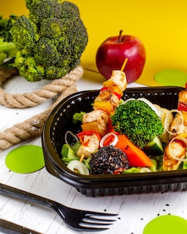 Vista lateral del pollo frito en brochetas con verduras frescas, brócoli y cebolla en una caja de entrega