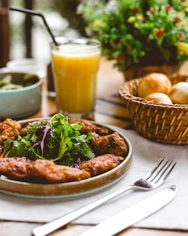 Vista lateral de pollo frito rebozado con verduras y jugo de naranja