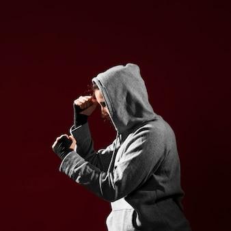 Vista lateral posición de combate de una mujer con capucha
