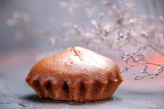 Vista lateral de primer plano cupcake sabroso cupcake junto a las ramas