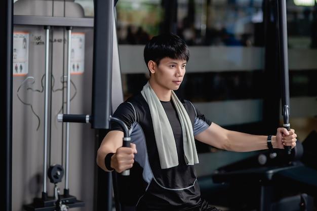 Vista lateral, primer plano retrato joven guapo en ropa deportiva sentado para hacer ejercicio de prensa de pecho de máquina en el gimnasio moderno, mirando hacia adelante,