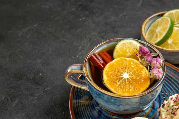 Vista lateral de primer plano té de hierbas té de hierbas con palitos de canela y limón en la taza azul junto al tazón de rodajas de limón sobre la mesa oscura