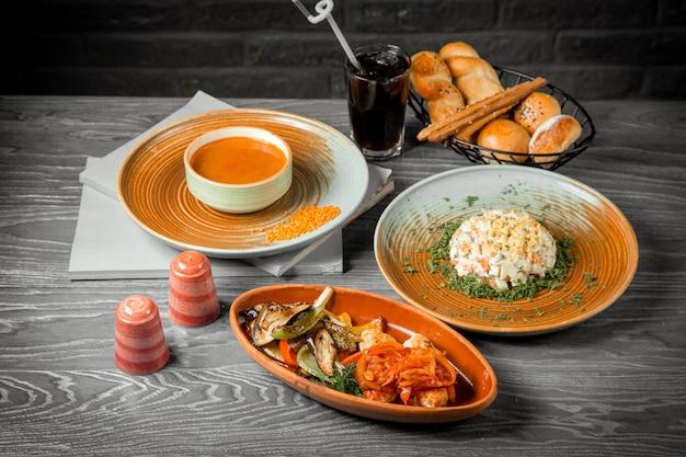Vista lateral del primer segundo plato principal y ensaladas albóndigas con verduras fritas con un refresco sobre la mesa