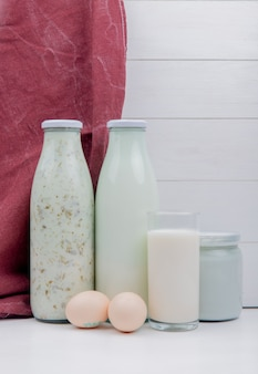 Vista lateral de productos lácteos como leche de sopa de yogurt azerbaiyano y leche agria coagulada con huevos sobre superficie blanca y superficie de madera