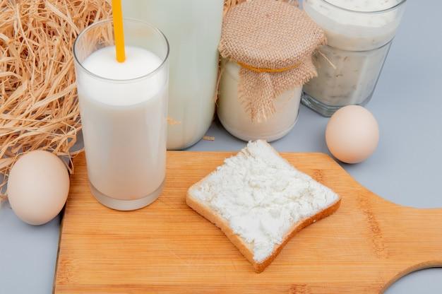 Vista lateral de los productos lácteos como queso cottage untado en rebanada de pan vaso de leche en la tabla de cortar crema de leche yogurt sopa y huevos con paja en la superficie azul