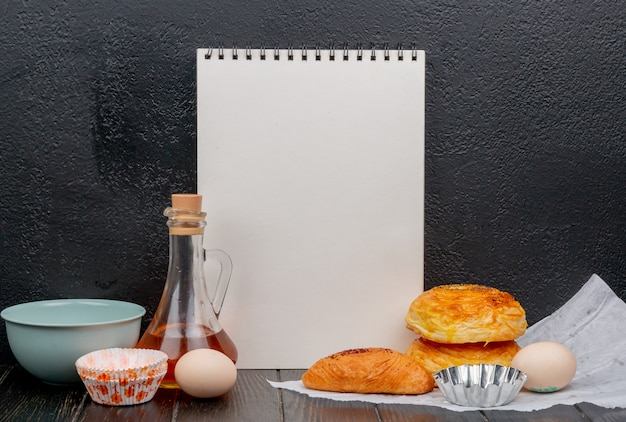 Vista lateral de productos de panadería como badambura goghal con harina huevo mantequilla y bloc de notas sobre superficie de madera y superficie negra con espacio de copia