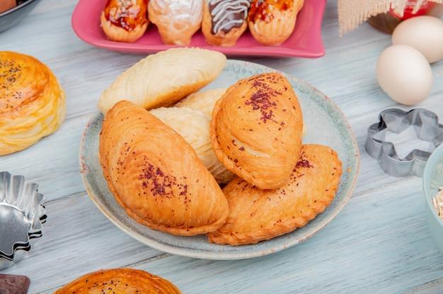Vista lateral de productos de panadería como badambura shakarbura goghal en placa huevos tortas en madera